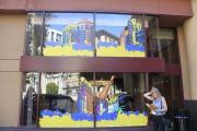 Attendee stands by exterior mural on Marriott window